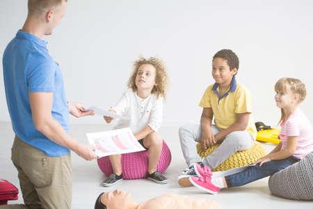 First aid instructor teaching children how to do resuscitation using phantom
