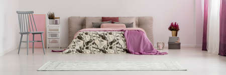 Grey chair next to king-size bed with patterned bedding and violet blanket between plants in bright bedroom