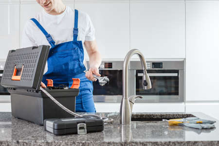 Close-up of plumber with wrench and black toolbox and gloves on kitchens countertop with faucet
