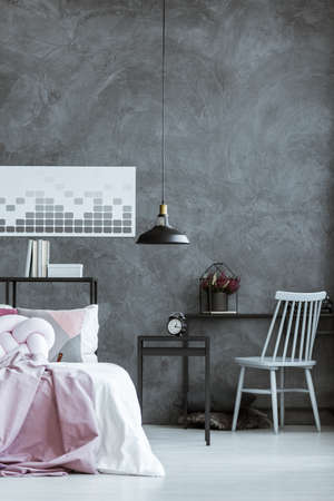 Grey chair at black desk with heather and clock on nightstand in dark bedroom with lamp and poster Фото со стока