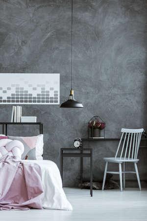 Grijze stoel bij zwart bureau met heide en klok op nachtkastje in donkere slaapkamer met lamp en poster