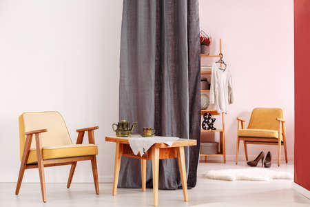 Wooden yellow chair next to a table with kettle in dining room interior with walk-in wardrobe behind grey cloth Stock Photo
