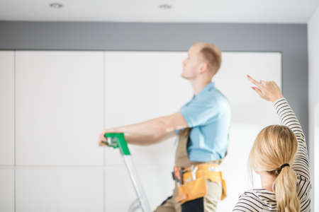 Housewife showing the fault to electrician in overalls standing on the ladder