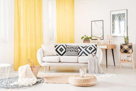 Kussens met geometrisch patroon liggend op een witte bank in een gezellige woonkamer met gele gordijnen