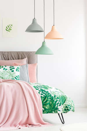 Pink pastel blanket and quilt with botanic print on bed