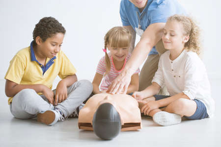 Children and paramedic have fun during first aid training with manikin
