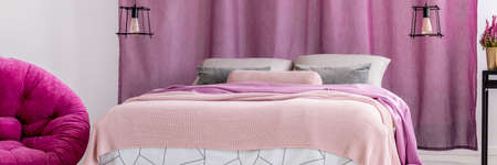Close-up of king-size bed with pink bedsheets and grey pillows against violet curtains in bedroom with lamps and pouf