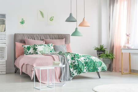 Pastel bedding on stylish bed in white bedroom with plants Stock Photo