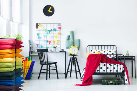 Colorful pillows in bright childs room with red blanket on the bed and yellow clock on a stool near desk with chair Banco de Imagens