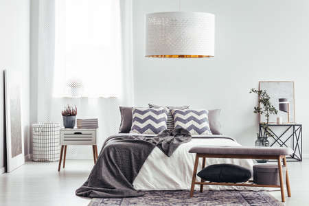 Patterned cushions and blanket on bed in bright bedroom interior with white lamp and plant on nightstand