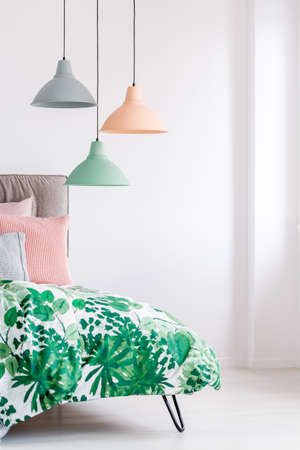 Coverlet with leaves print on a bed in minimalist, pastel bedroom Banque d'images