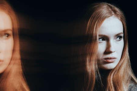 精神病と分裂した性格を持つ苦しむ少女。黒い背景に対するぼやけた複数の顔の写真