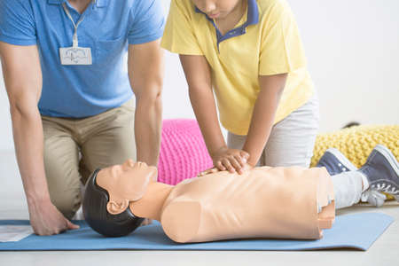 Afro-american boy reanimating a manikin during first aid training with paramedic Stock Photo