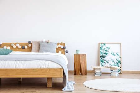 Piles of books placed on the floor in white bedroom with poster and wooden bedside table