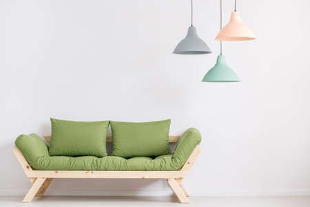 Wooden sofa with green pillows in empty room with white wall