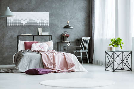 Plant on designer table in bright bedroom with grey and pink bedsheets on bed in bedroom with workspace and poster on wall