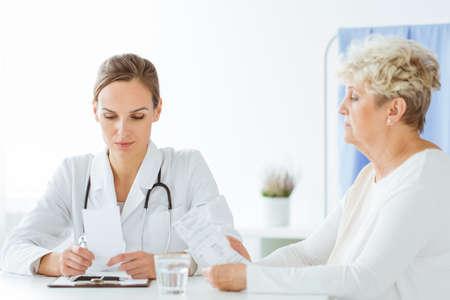 Algemene arts die bloedonderzoekresultaten raadplegen met droevige patiënt in het ziekenhuis Stockfoto