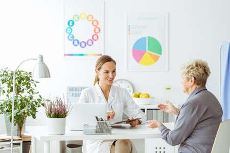ポスター付き明るいオフィスで患者と相談中に制服姿の栄養士