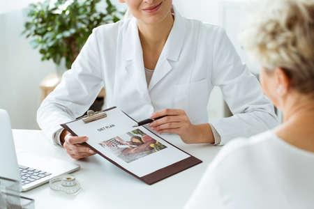 Close-up van voedingsdeskundige die een gepersonaliseerd dieetplan voor een patiënt houden tijdens afspraak in de kliniek Stockfoto