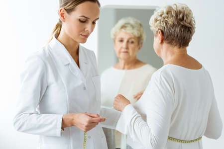 Nutritionist measuring patients body circumference. Unsatisfied woman looking in the mirror Stock Photo