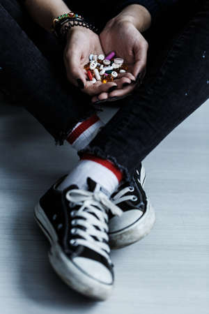 High angle of teenager wearing black trainers holding pills in her hands
