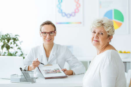 Diabetic during appointment with professional nutritionist holding a diet plan in the clinic
