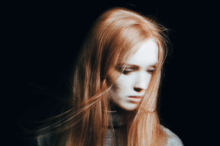 Blurred face of a girl who is a victim of violence against black background