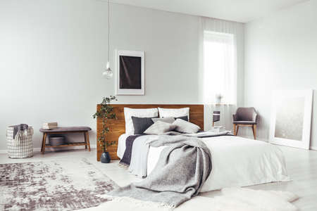 Dark poster on the wall with copy space in bright bedroom interior with bench, grey chair and patterned carpet Stok Fotoğraf - 93386581