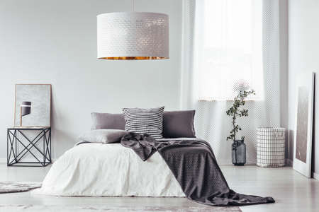 Patterned blanket and pillow on bed and table in designer bedroom interior with white lamp and window Standard-Bild