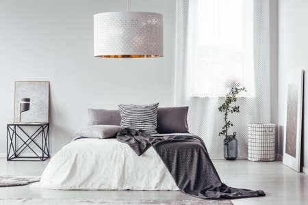 Manta estampada e travesseiro na cama e mesa no interior do quarto designer com lâmpada branca e janela