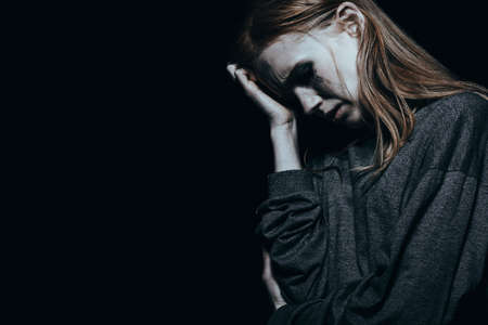 Depressed woman with anxiety against black background with copy space