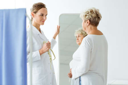 Professional dietitian with measure tape and unhappy woman standing in front of a mirror