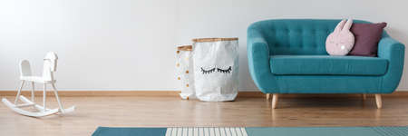 White rocking horse and blue sofa with pillows in kids room with paper bags against wall with copy space