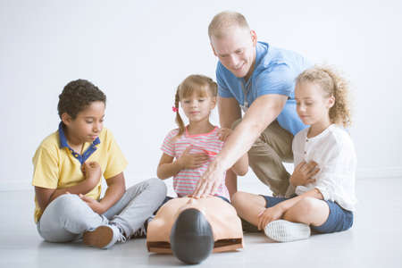 First aid trainer presenting reanimation technique on manikin to group of multiethnic children