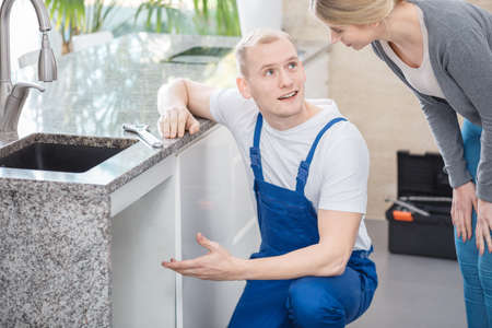 Sanitation expert consulting the glitch with housewife in the kitchen with wrench on countertop Stok Fotoğraf