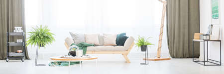 Beige sofa with decorative cushions standing next to the window in bright, natural living room interior Stock Photo