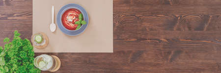 Wooden spoon lying next to red soup in a blue bowl with basil leaves Stok Fotoğraf - 93386969