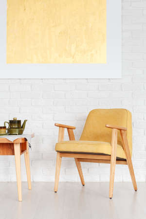 Retro yellow chair next to a wooden table with kettle against white brick wall with gold painting in dining room interior
