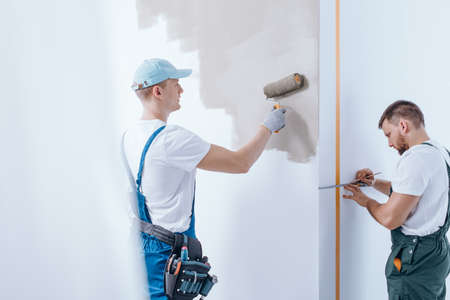 Painter with tool belt painting the wall and his colleague measuring the wall during finishing interior Stock Photo