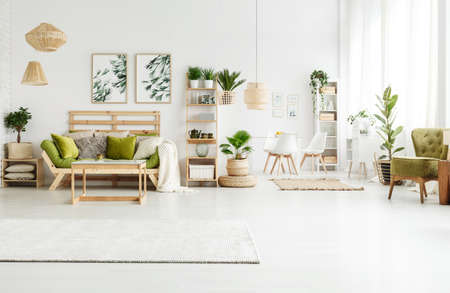 Bright rug, leaves posters and pouf in spacious green apartment interior with sofa, plants and armchair