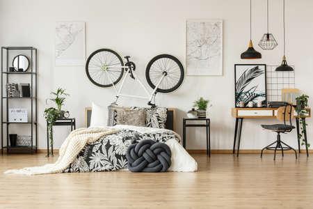 Chaise en bois contre un bureau dans une chambre à la mode noire et blanche pour adolescent avec vélo, plantes et décorations à motifs