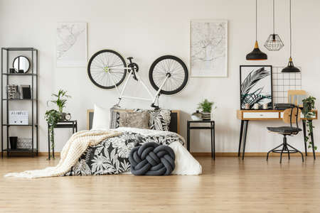 Wooden chair against desk in trendy black and white bedroom for teenager with bike, plants and patterned decorations Stockfoto