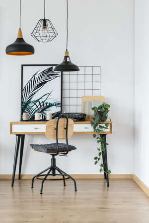 Modern retro style desk and chair in cozy white home office interior with vintage typewriter, plant and poster