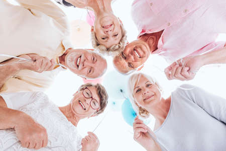 Low angle of smiling seniors standing in a circle and celebrating together Stockfoto