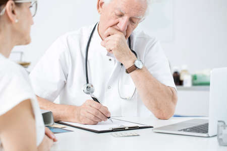 Surgeon in white uniform giving expert opinion before the patients surgery