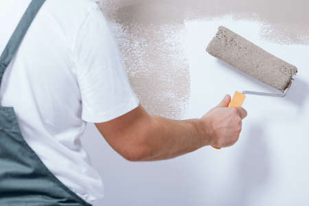 Close-up of handyman holding a roller in his hand and painting white wall beige