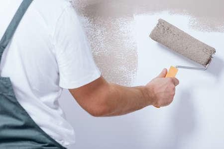 Close-up van manusje van alles dat een rol in zijn hand houdt en wit muurbeige schildert Stockfoto