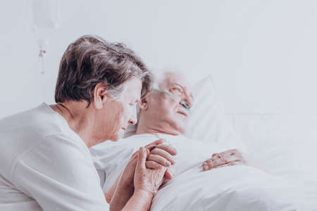 Elder married couple sitting in the hospital holding hands and praying