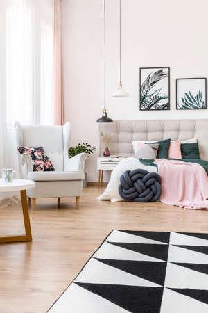 Bloemenhoofdkussen op leunstoel en zwart-wit tapijt in verfijnd slaapkamerbinnenland met lampen boven bed en nightstand Stockfoto