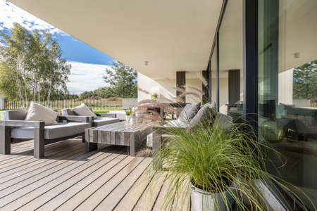 Grey garden furniture on board floor on terrace of spacious apartment with view of neighborhood